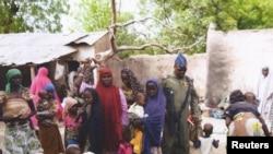 Seorang tentara Nigeria berbicara dengan beberapa perempuan dan anak-anak yang berhasil diselamatkan dari Boko Haram di Yola, 29 April. Militer Nigeria kembali berhasil menyelamatkan ratusan perempuan dan anak-anak pada 30 April. (REUTERS)