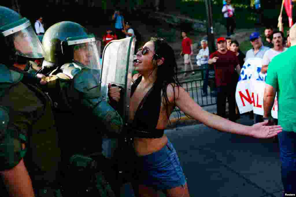 A demonstrator confronts riot police during a rally in defense of the nationalization of lithium reserves in the country, in Santiago, Chile, Jan. 29, 2018.