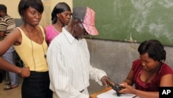 Warga di dekat Rundu, Namibia, mencelupkan jarinya di tinta setelah memberikan suara dalam pemilu (28/11). (AP/Dirk Heinrich)