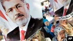 8月19日在埃及开罗举行的示威中,抗议者举着被推翻的总统穆尔西的画像
