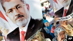 被罷黜的埃及總統穆爾西的支持者舉起穆爾西的海報 (資料照片)