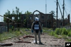 An OSCE monitor checks the territory for mines during a patrol in Shyrokyne, Donetsk region eastern Ukraine, Saturday, July 4, 2015. (AP Photo)