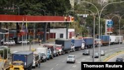 Camiones de remolque se alinean a lo largo de una avenida para llenar sus tanques en una estación de servicio en medio de la escasez de diesel, en Caracas, Venezuela. Marzo 5, 2021. Foto: Reuters.