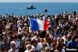 A French flag flies among the crowd as people gather in front of the Monument du Centenaire during a minute of silence on the third day of national mourning to pay tribute to victims of the truck attack along the Promenade des Anglais on Bastille Day that