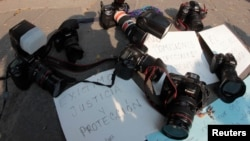 FILE - Journalists leave their cameras on posters demanding justice and protection during a protest against murder of Regina Martinez, journalist and correspondent for the Mexican magazine Proceso, in Puebla on April 29, 2012.