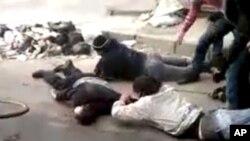 Men retrieve a body, in a rubbish-strewn street in Homs, Syria December 15, 2011.