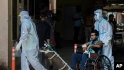 Petugas kesehatan mengenakan APB memindahkan pasien COVID-19 di sebuah rumah sakit pemerintah di Gauhati, India, Senin, 24 Mei 2021. (Foto: AP)