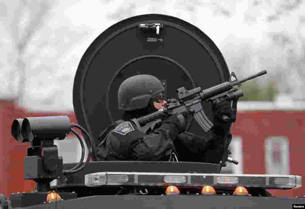 Un miembro del equipo SWAT dirige su arma contra uno de los edificios del vecindario en Watertown durante la búsqueda del sospechoso.