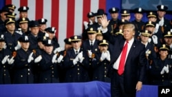 President Donald Trump waves after speaking to law enforcement officials on the street gang MS-13, July 28, 2017, in Brentwood, New York.