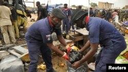 Des agents de sécurité assistent les victimes d'une explosion à Sabon Gari, Kano, Nigeria, 24 juillet 2014
