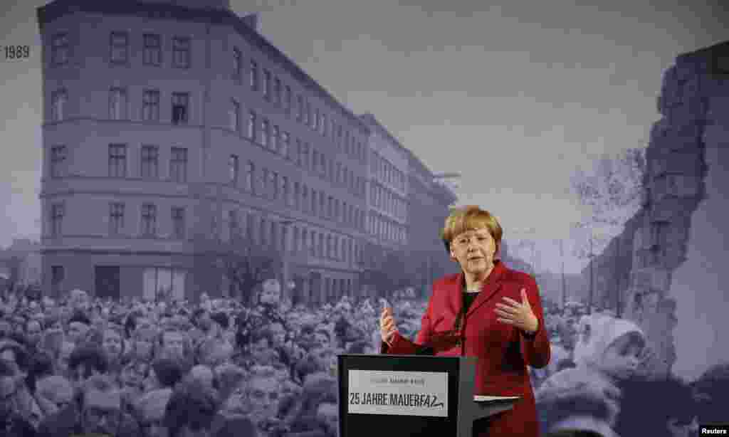 German Chancellor Angela Merkel speaks in front of a photograph showing Bernauer Strasse in November 1989 at the exhibition opening during a ceremony marking the 25th anniversary of the fall of the Berlin Wall at a memorial in Bernauer Strasse Berlin, Germany.