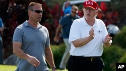 FILE - President Donald Trump walks with Gene Gibson, commanding officer at Coast Guard Station Lake Worth Inlet, as he arrives, Dec. 29, 2017, to meet with members of the U.S. Coast Guard, who he invited to play golf, at Trump International Golf Club, in West Palm Beach, Fla.
