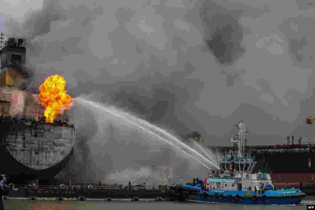 Fire fighters onboard a vessel extinguish a fire on a tanker ship docked in Belawan, Indonesia.