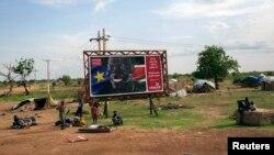 Warga sipil bersiap untuk meninggalkan tempat tinggalnya untuk menghindari kekerasan di wilayahnya, berkumpul di depan papan yang menayangkan poster perayaan kemerdekaan Sudan Selatan yang ke-2 di Bentiu, Sudan Selatan, 20 April 2014 (Foto: dok).