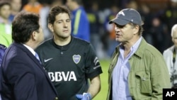 FILE - In this May 14, 2015, photo, Argentine businessman Alejandro Burzaco (R) is seen talking to a soccer official and a goalkeeper at a stadium in Buenos Aires, Argentina.
