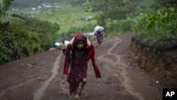 A child carries supplies up a muddy mountainside in Nuevo Queja, Guatemala, Thursday, July 8, 2021. (AP Photo/Rodrigo Abd)