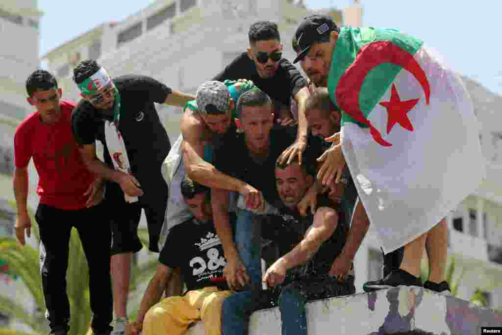 Demonstrators spray water on a man who tried to self-immolate himself during a protest demanding the removal of Algeria's ruling elite, in Algiers.