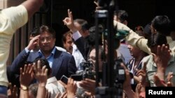 Pakistan's former President Pervez Musharraf (L) salutes his supporters as he leaves after his appearance before the district High Court in Karachi March 29, 2013. The Sindh High Court on Friday granted a bail extension to Musharraf, local media reported.