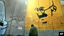 A Palestinian taxi driver prays in front of a section of Israel's separation barrier with a depiction of the late Indian non-violence advocate Mahatma Gandhi (file photo)