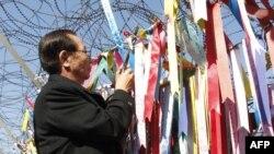 Ông Shigeo Iizuka, 72 tuổi, người anh em của một công dân Nhật Bản được cho là bị Bắc Triều Tiên bắt cóc, buộc dải ruy băng lên hàng rào thép gai ở khu phi quân sự phân chia hai miền Triều Tiên.