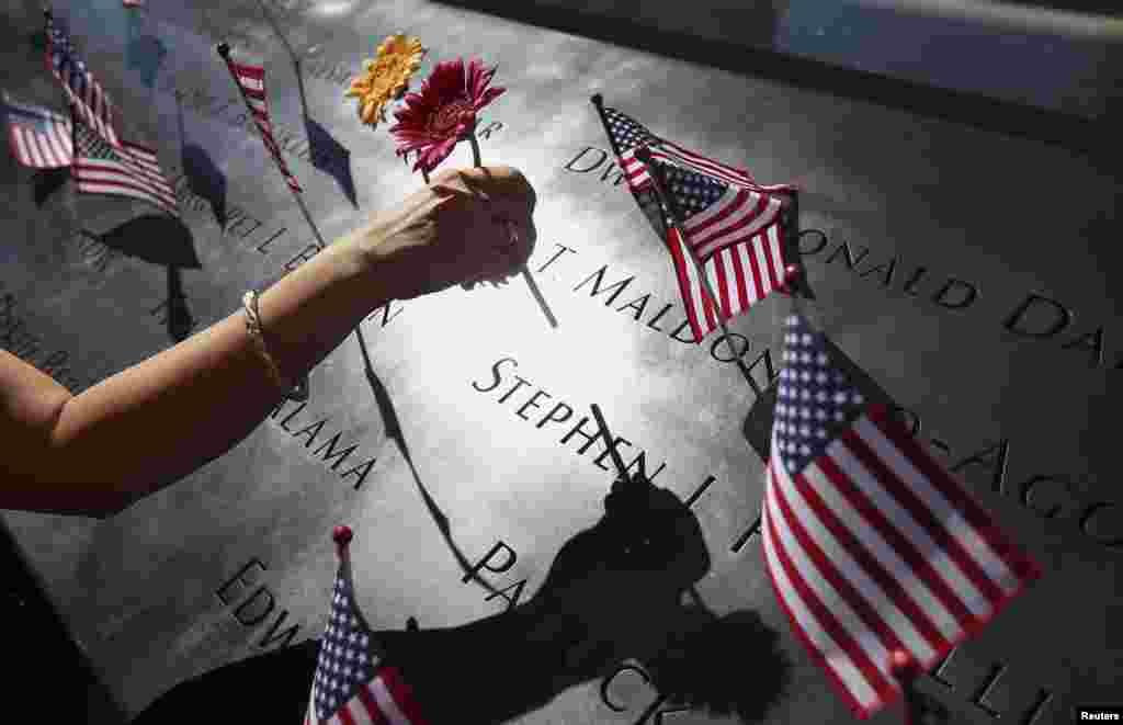 Los familiares y amigos de las víctimas dejan sus tributos en los nombres de las víctimas, grabados en torno a las dos fuentes de agua del memorial.