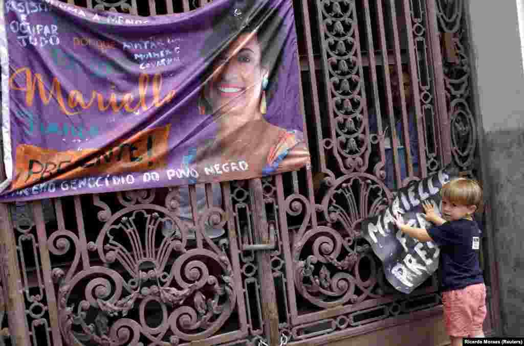 Um menino segura um cartaz junto à fotografia da vereadora Marielle Franco, assassinada a tiros a 14 de Março. Rio de Janeiro