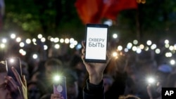 """Demonstrators wave their cellphones as they protest plans to construct a cathedral in a park in Yekaterinburg, Russia, May 15, 2019. The words on the phone pictured say, """"Park has to be!"""""""