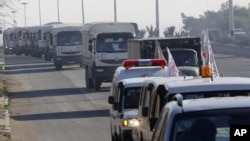 FILE - A convoy of trucks loaded with humanitarian supplies are seen heading to the besieged town of Madaya, about 40 kilometers northwest of Damascus, Syria, for a U.N.-aid distribution, Jan. 14, 2016.