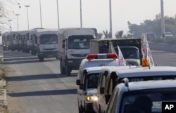 FILE - A convoy of trucks loaded with humanitarian supplies are seen heading to the besieged town of Madaya, 24 kilometers southwest of Damascus, Syria, for a U.N.-aid distribution, Jan. 14, 2016.