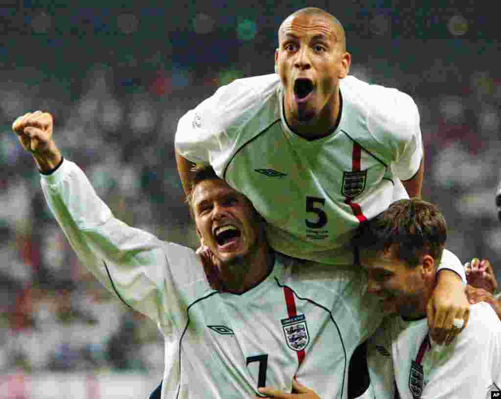 David Beckham, left, Rio Ferdinand, top, and Michael Owen celebrate the team's second goal scored by Owen during the 2002 World Cup second round match against Denmark in Niigata, Japan, June 15, 2002.