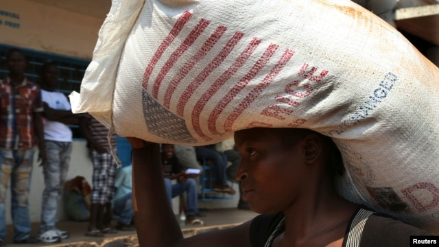 A displaced refugee woman carries a rice bag after receiving it as humanitarian aid at the airport outside the capital Bangui, Jan. 7, 2014.