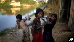 FILE - Rohingya girls carry water pots at Kutupalong refugee camp, in Cox's Bazar, Bangladesh, Nov. 19, 2017.