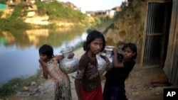 FILE - Rohingya girls carry water pots at Kutupalong refugee camp in Bangladesh, Nov. 19, 2017. Women and girls in this and other camps are often targets of traffickers.