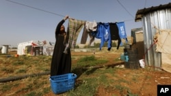 A Syrian refugee woman hangs laundry at a Syrian refugee camp in the eastern Lebanon on June 19, 2014.