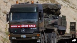 FILE - A Turkish military truck is seen transporting a mobile missile launcher to the Syrian border, near Kilis, Turkey.
