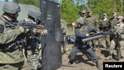 FILE - Ukrainian soldiers and servicemen of the U.S. Army's 173rd Airborne Brigade Combat Team take part in joint military exercises in Yavoriv, western Ukraine, May 12, 2015.