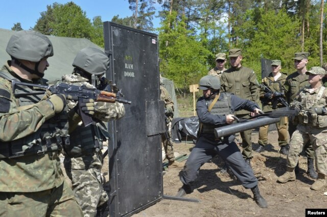 FILE - Ukrainian soldiers and servicemen of the U.S. Army's 173rd Airborne Brigade Combat Team take part in a joint military exercises in Yavoriv, outside Lviv, Ukraine, May 12, 2015.