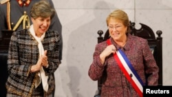 FILE - Chile's President Michelle Bachelet smiles next to Senate President Isabel Allende (L), daughter of late former President Salvador Allende, after delivering her annual address at the national congress building in Valparaiso city, northwest of Santiago, May 21, 2014.
