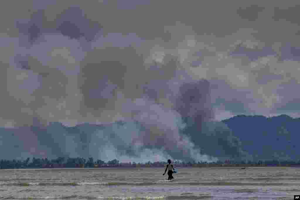 Asap tampak mengepul dari kawasan permukiman negara bagian Rakhine, Myanmar, yang ditinggal mengungsi oleh warga etnis Rohingya, terlihat dari Shah Porir Dwip, Bangladesh.