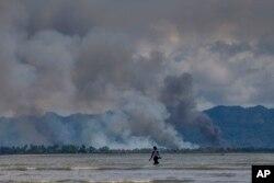 A Bangladeshi boy walks towards a parked boat as smoke rises from across the border in Myanmar, at Shah Porir Dwip, Bangladesh, Sept. 14, 2017.