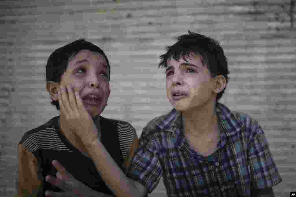 Zeid Ali, 12, left, and Hodayfa Ali, 11, comfort each other after their house was hit and collapsed during fighting between Iraqi forces and Islamic State militants in Mosul, Iraq, June 24, 2017. The Ali cousins said some of their family members were still under the rubble.