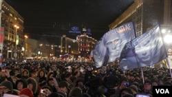 Para pendukung Putin mendengarkan pidato kemenangan Putin di Moskow (4/3).