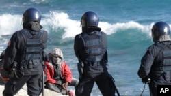 Un migrant confronté à des policiers italiens en tenue anti-émeute après l'évacuation d'un campement à la frontière franco-italienne à Ventimiglia, en Italie, 30 septembre 2015