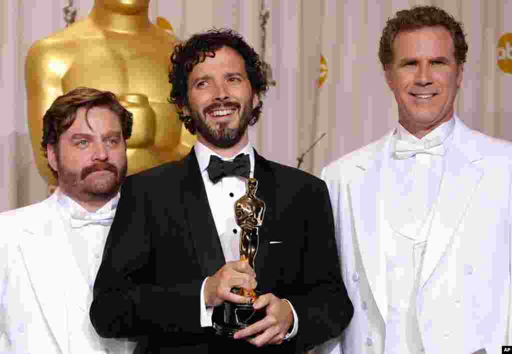 """Брет МекКензи, во центар со презентерите Зак Галифианакис и Вил Ферел, и неговата награда за најдобра оригинална песна за """"Човек или Мапет"""" (AP)"""