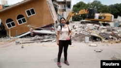 FILE - Ana Maria Hernandez, 37, a clothing salesperson, stands outside her house as it is demolished after an earthquake in Jojutla de Juarez, Mexico, Sept. 30, 2017.