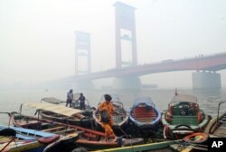 FILE - A woman disembarks from a boat as the Ampera Bridge is shrouded in haze from wildfires in Palembang, South Sumatra, Indonesia, Sept. 29, 2015.