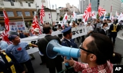"FILE - Nationalist protesters, at rear, march through a Tokyo street to denounce ""privileges"" for Koreans living in Japan, past a counterprotester, bottom right, who yells at them. Extremist groups sometimes take to Tokyo streets, waving militarist rising-sun flags and chanting anti-Korean slogans."