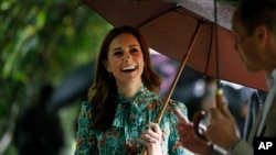 FILE - Britain's Prince William and his wife Kate, Duchess of Cambridge smile as they walk through the memorial garden in Kensington Palace, London, Aug. 30, 2017.