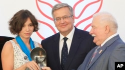 Zhanna Nemtsova, left, the daughter of slain Russian opposition leader Boris Nemtsov stands together with Poland's President Bronislaw Komorowski center, and former president. Lech Walesa, right, after receiving Poland's 4 million zlotys ( US $1 million