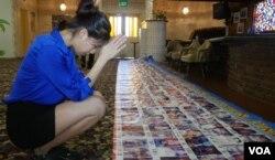 林韵珊在失踪中国孩童海报前祈祷。(美国之音国符拍摄)